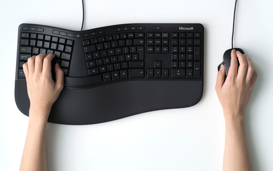 Hands lying on a Microsoft Ergonomic keyboard and a Pro IntelliMouse
