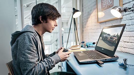 男孩手中握著控制器,在筆記型電腦上玩 Xbox Live。