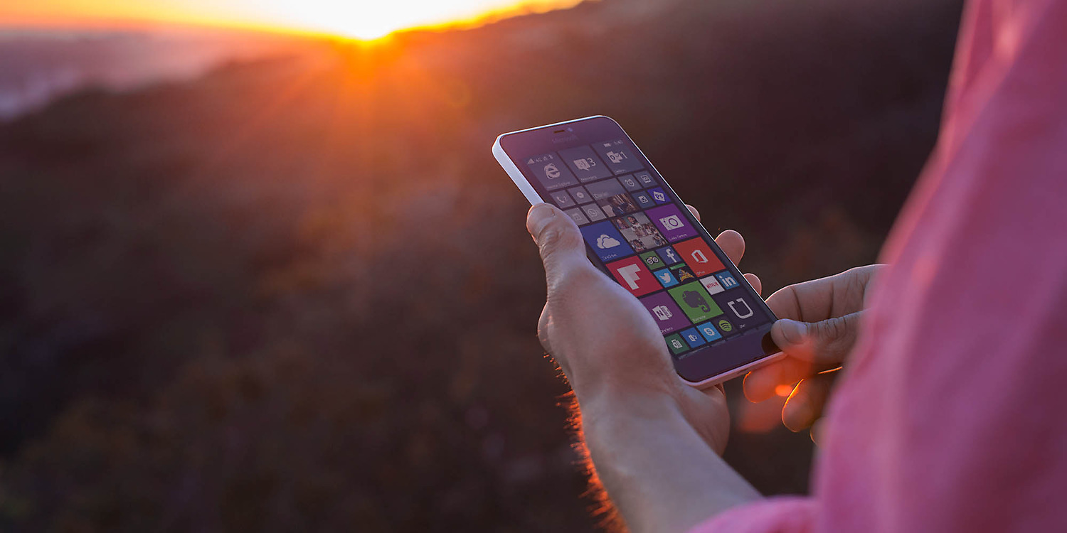 Man's hands holding a Lumia 640 XL with start screen on the display with a beautiful sunset in the background