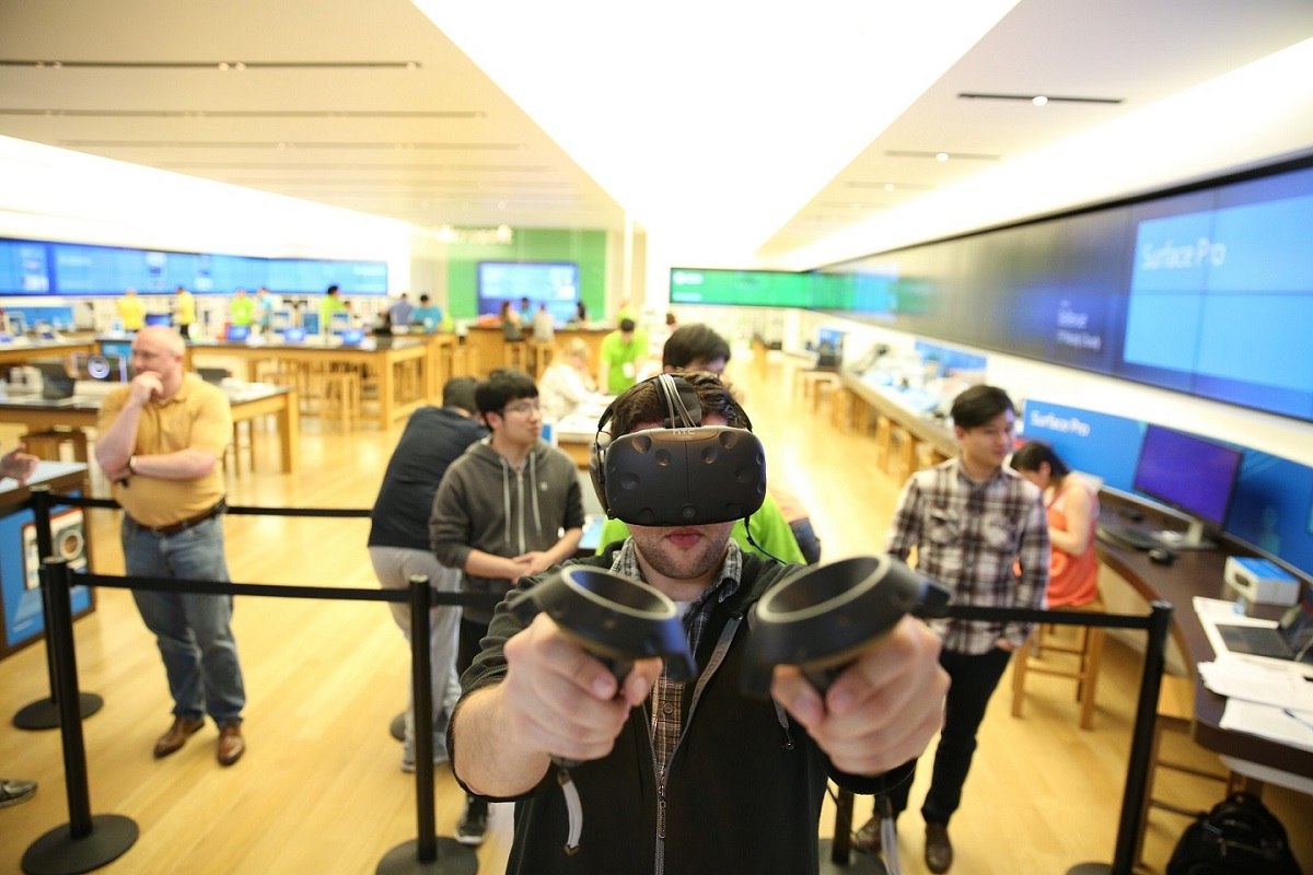 A man wearing HoloLens and holding controllers in front of camera