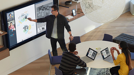 Man drawing on Surface Hub with Skype on screen, and two students sit at a table with Surface Books.
