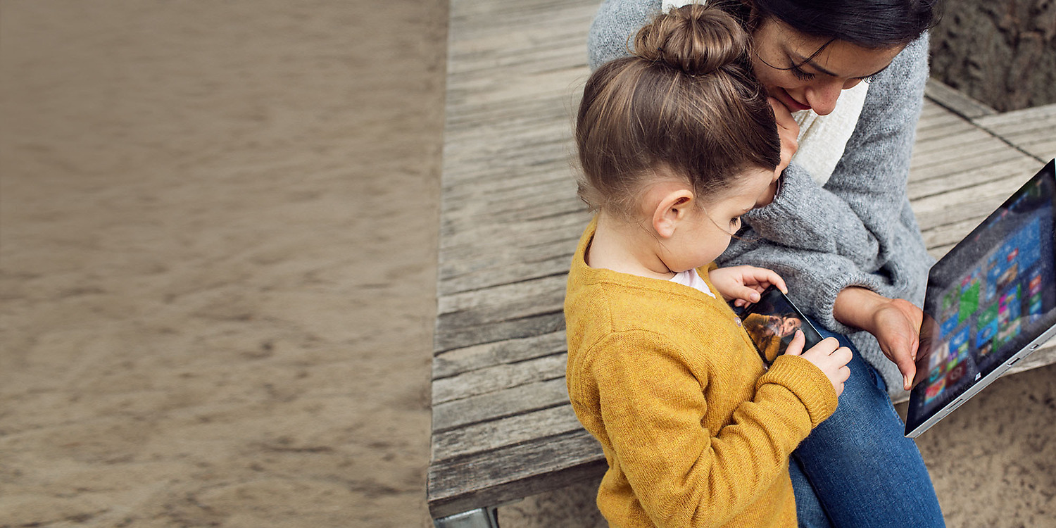 Mother and daughter on playground with the mother holding  a Surface tablet as they both look at Lumia phone screen