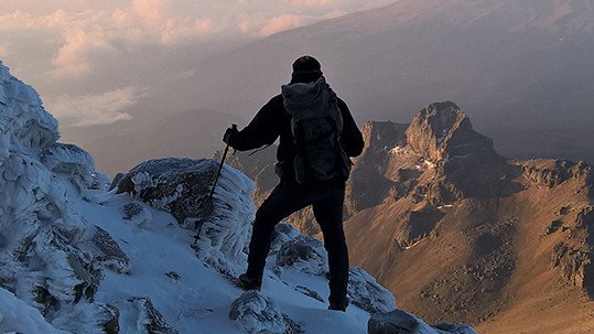 Mann på vandring mot toppen av et fjell.