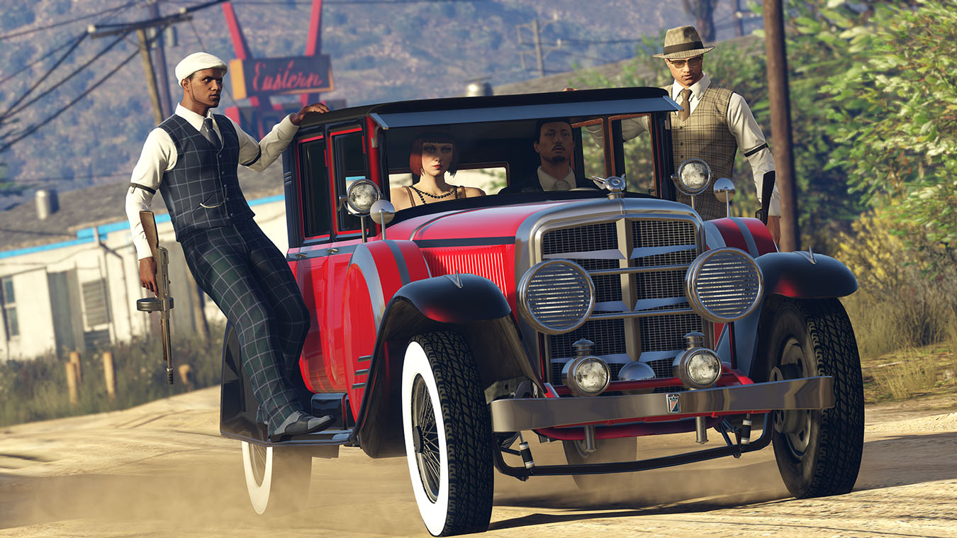 two players hold onto side of 1920s style car while driving down dirt road