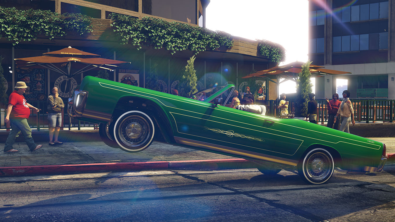 Side view of green low rider style car mid hop