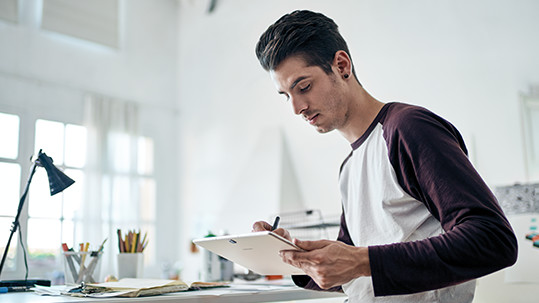 A man using a detachable pen on his tablet while sketching designs in a work setting.