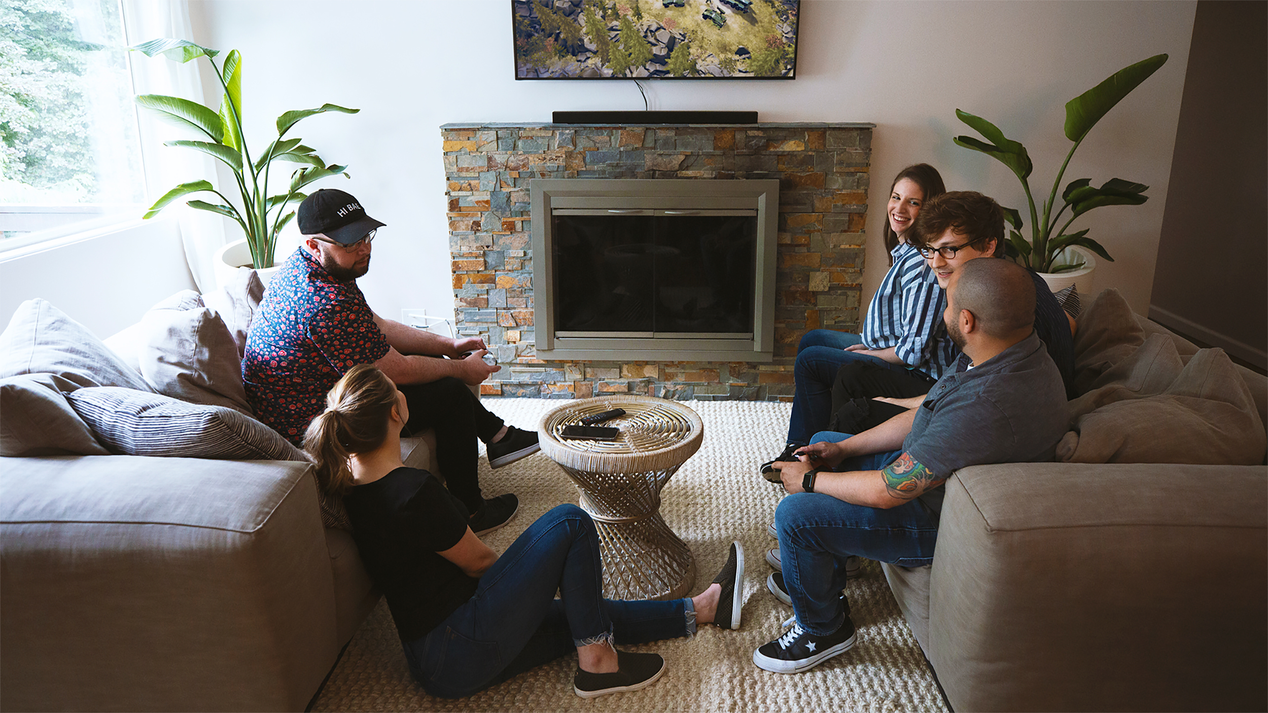 Three friends hanging out near the kitchen island. One person showing off their newest Xbox achievement on their phone to the other two people.