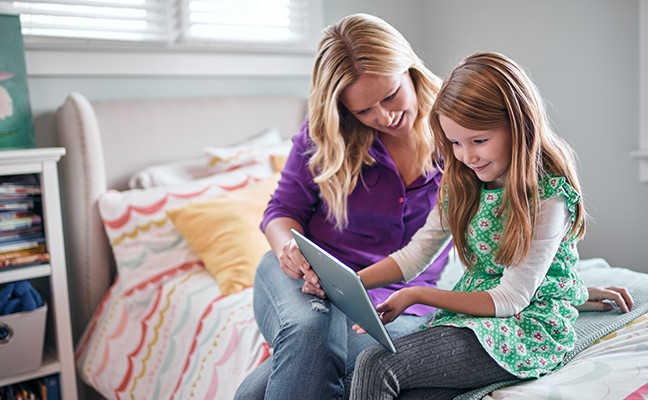 A mother and daughter sitting on a bed watching a moving on their tablet.