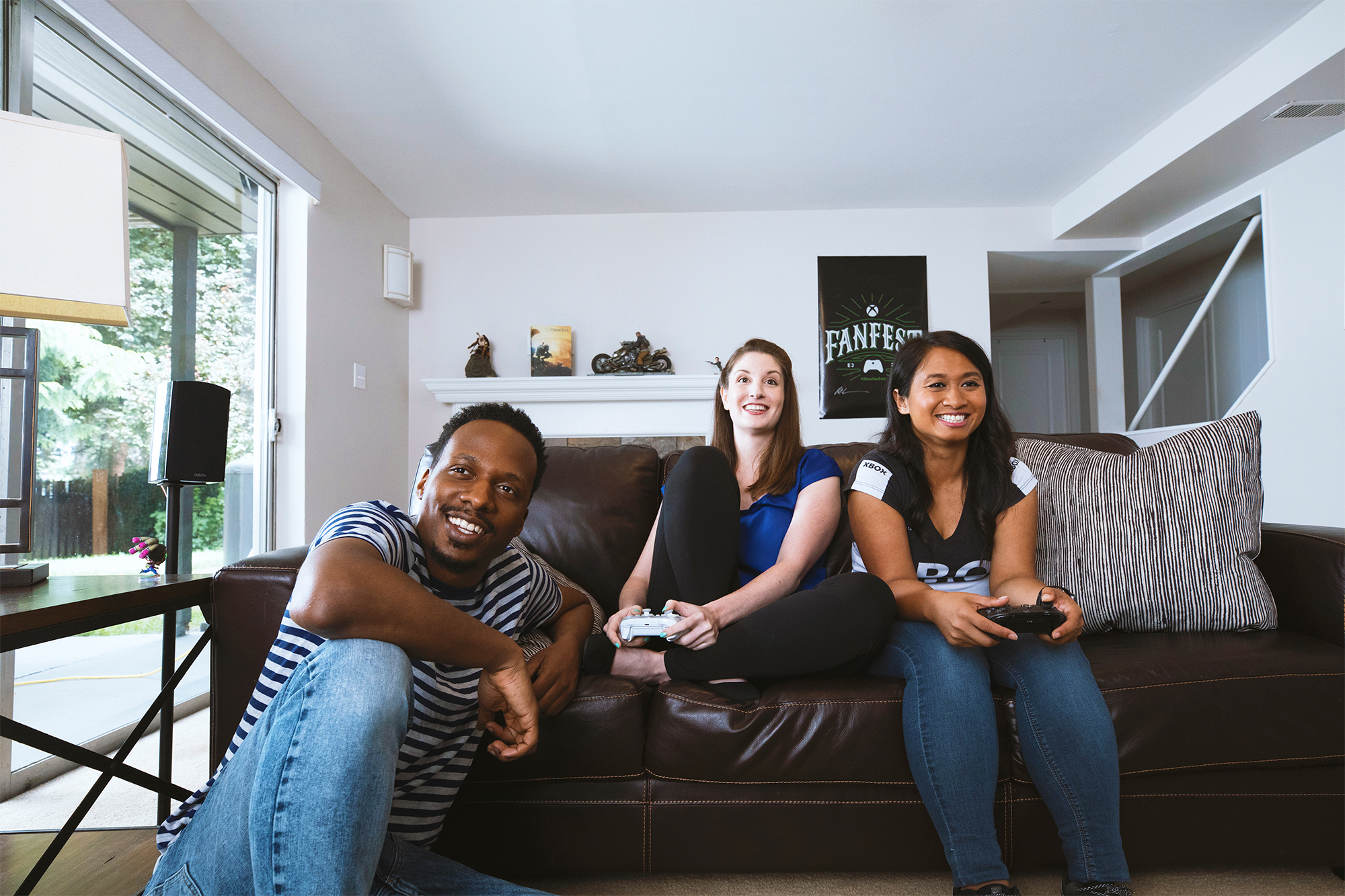 Two women playing video games sitting on a couch while a man is sitting nearby hanging out and watching them play