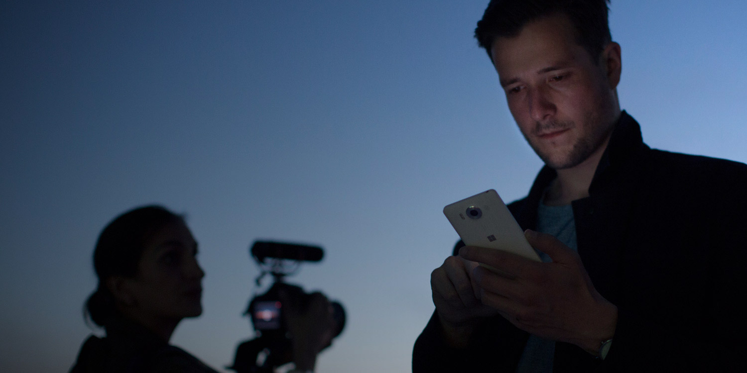 Man looking at white Lumia 950 screen at sunset with woman holding camera in background