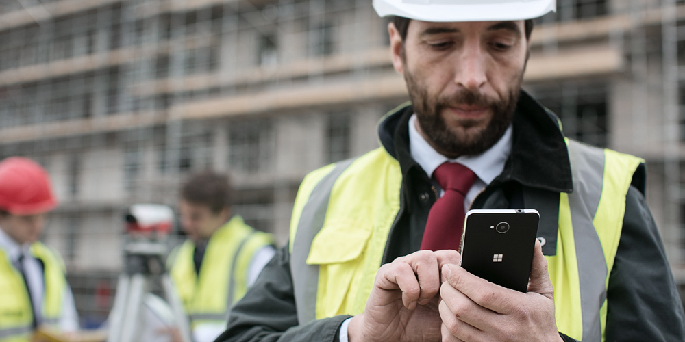 Man in hard-hat, looking at his Lumia phone at construction site