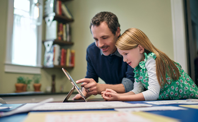 A father using the touch screen on a tablet with his daughter.
