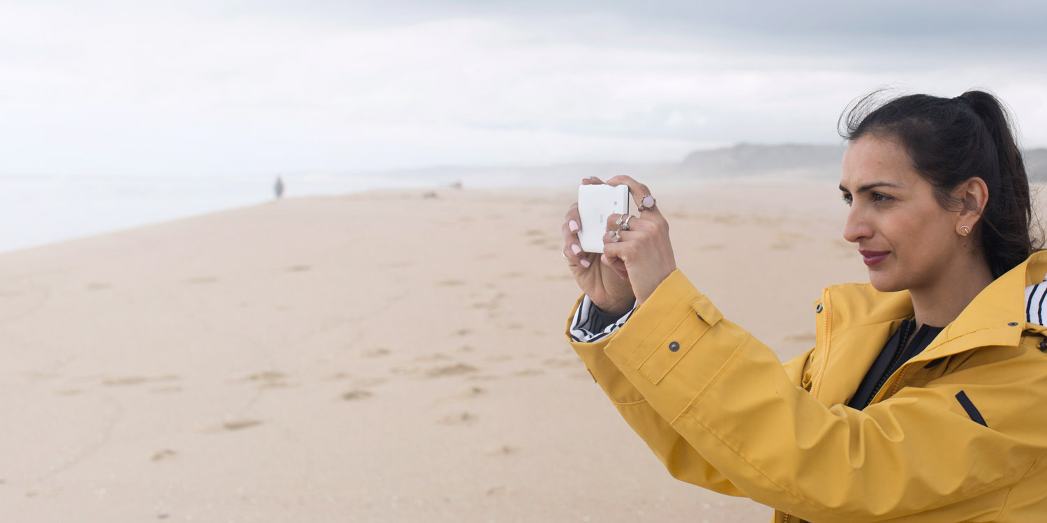 Woman wearing raincoat taking a photo of the surf on a cloudy beach