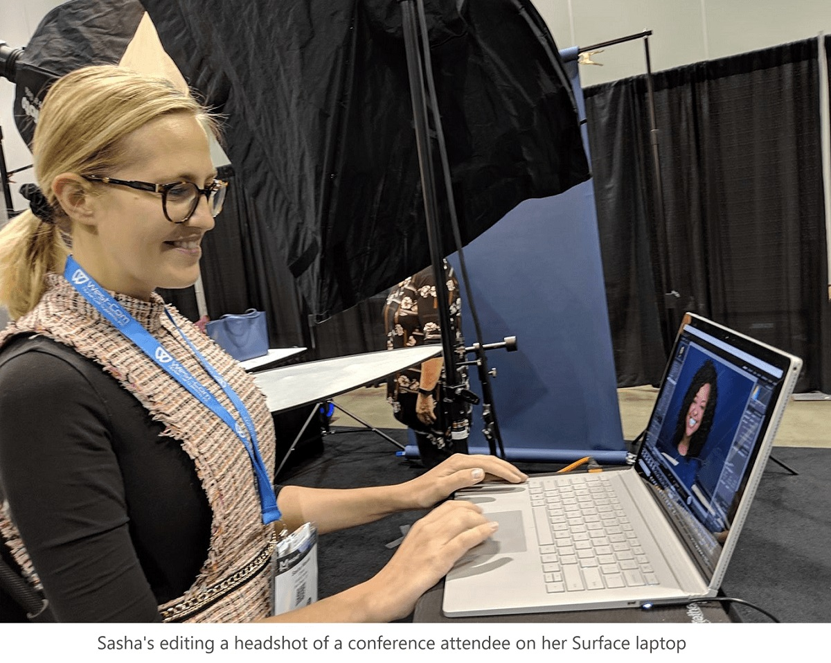 Sasha is editing a headshot of a conference attendee on her Surface laptop